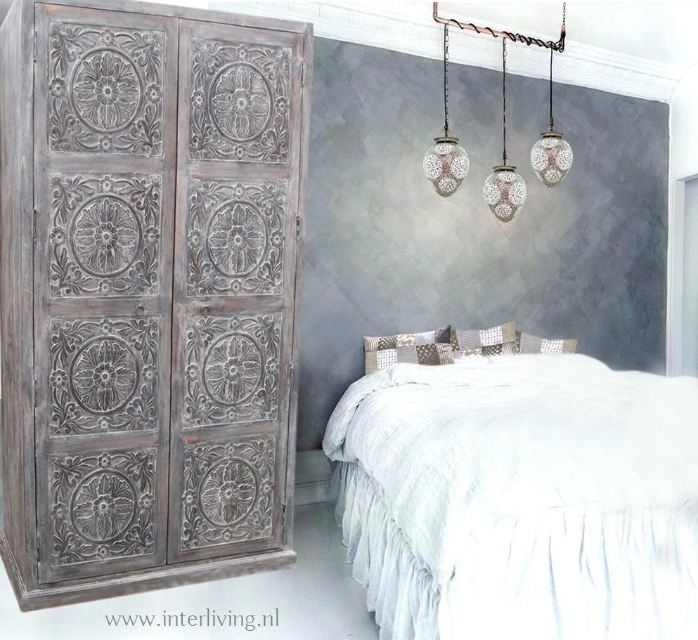 oosterse slaapkamer in stijl: hoge grijze Indiase kast met lotusbloemen