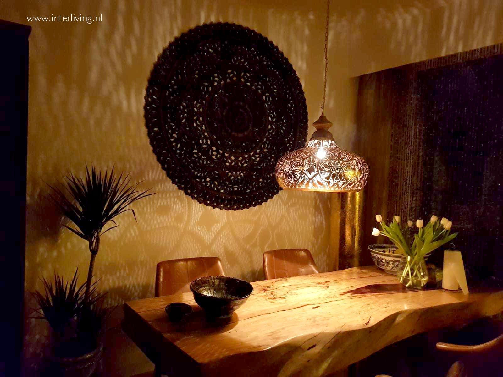 oosters paneel boven eettafel met gaatjeslamp